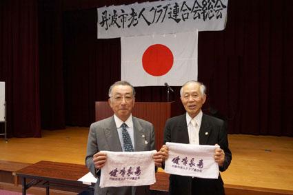 総会にて 総会の横断幕も会長の直筆 写真右から矢田貝会長、吉見氏